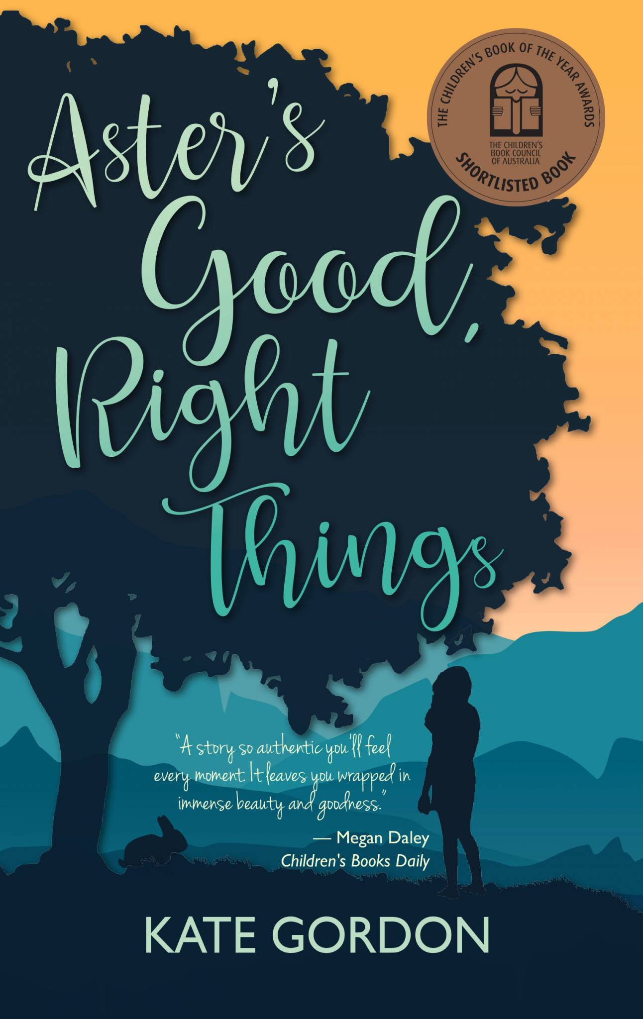 Book Cover for children's book Aster's Good, Right Things. The title is written in cursive writing in green through the centre of the page. The background is a silhouette of a large tree with a girl and a rabbit standing underneath it. There is an orange sky and hills behind the silhouette